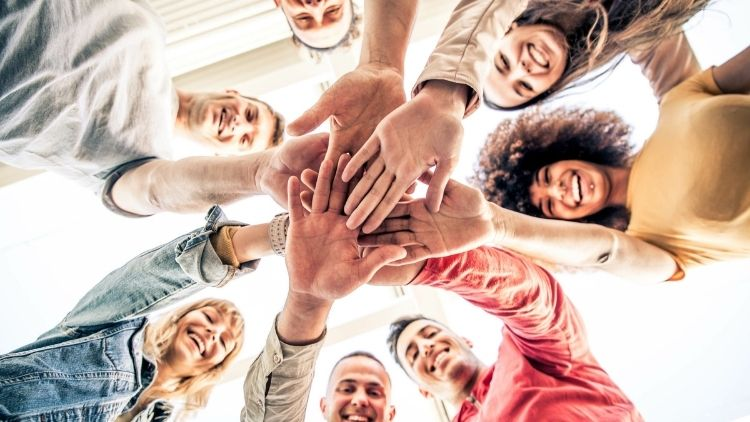 people of all ethnicities with their hands together in a circle smiling