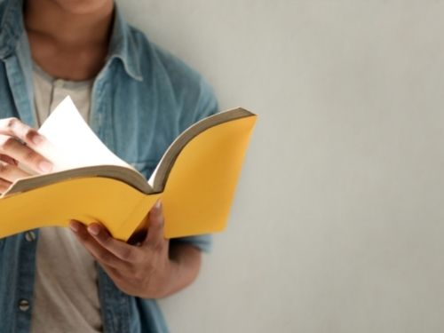 young man wearing blue collared shirt over a white tee reading a book with a yellow cover