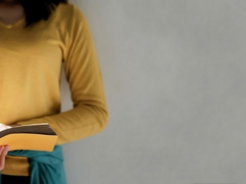 young woman wearing yellow reading a book with a yellow cover