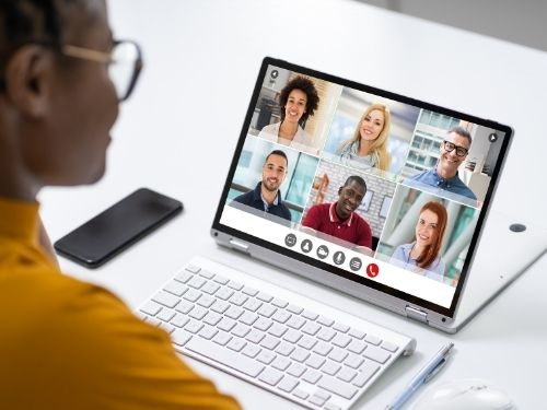 woman of color with glasses looking at screen of the gallery view of a virtual meeting